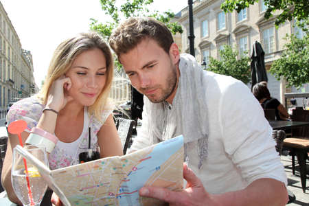 Couple sitting at a coffee shop terrace to look at map Фото со стока