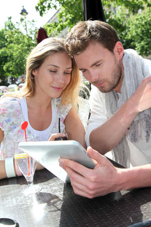 Couple sitting at a restaurant terrace with electronic tablet photo