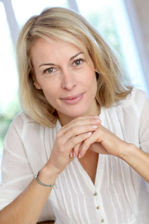 Portrait of blond mature woman relaxing in sofa Reklamní fotografie