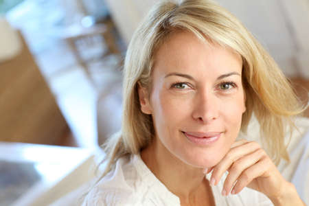 Portrait of blond mature woman relaxing in sofa Stock Photo