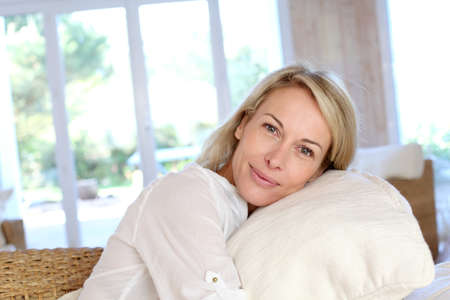 Portrait of blond mature woman relaxing in sofa Stock fotó