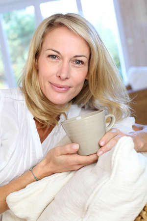 Mature blond woman in couch having a tea photo