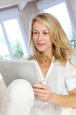 Beautiful mature woman using electronic tablet at home photo