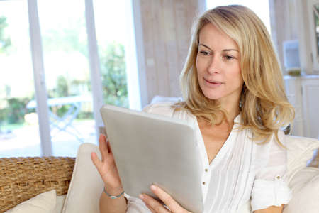 electronic tablet: Beautiful mature woman using electronic tablet at home Stock Photo