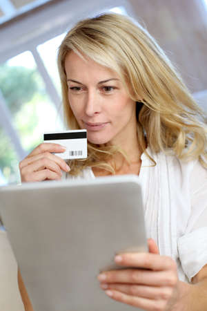 Blond mature woman doing online shopping photo