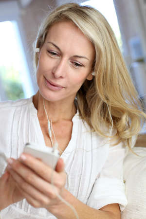 Middle-aged woman talking on mobile phone with handfree device photo