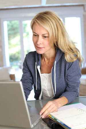 Middle aged blond woman working at home with laptop Stock Photo - 13904860