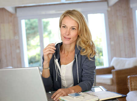 40 years old: Attractive middle-aged woman working at home Stock Photo