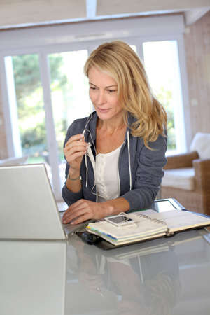 telework: Attractive middle-aged woman working at home Stock Photo