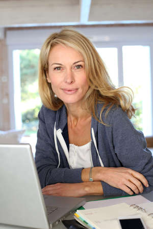 Middle aged blond woman working at home with laptop photo