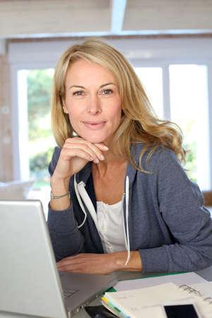 old technology: Donna di mezza et� bionda che lavora a casa con il computer portatile