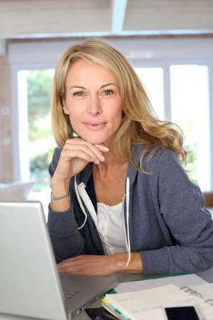 Middle-aged blond woman working at home with laptop photo