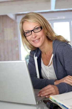 damas antiguas: Mujer de mediana edad rubia de trabajo en casa con ordenador port�til Foto de archivo