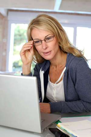 Middle-aged blond woman working at home with laptop Stock Photo - 13904674