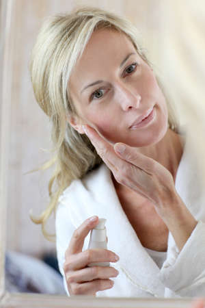 woman bathrobe: Attractive middle-aged woman applying comestics on her face