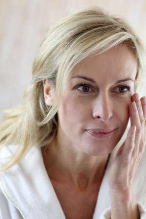 arrugas: Atractiva mujer de mediana edad comestics aplicar en el rostro Foto de archivo
