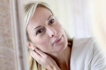 damas antiguas: Atractiva mujer de mediana edad comestics aplicar en el rostro Foto de archivo