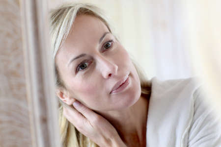 Attractive middle-aged woman applying comestics on her face photo