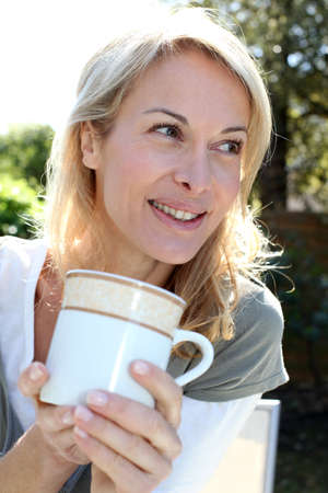Portrait of blond woman with tea mug sitting outside photo