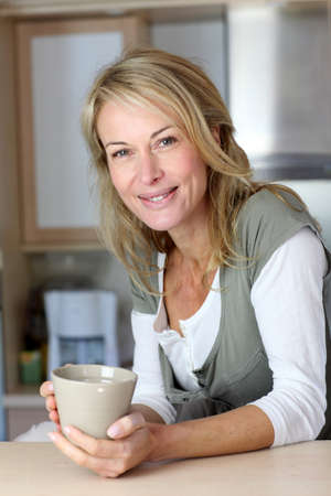 Attractive adult woman holding mug in home kitchen