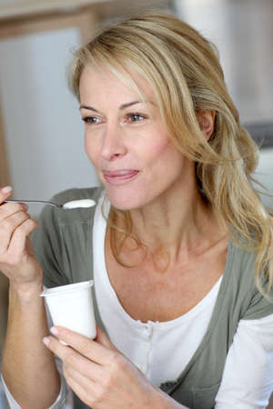 Portrait of middle-aged woman eating yoghurt photo