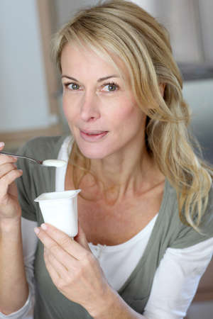 mid morning: Portrait of middle-aged woman eating yoghurt Stock Photo