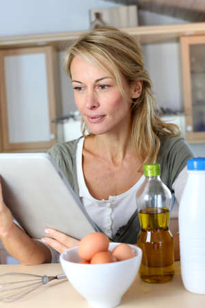Woman in kitchen looking at dessert recipe on internet Stock Photo - 13904872