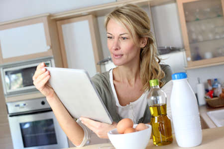 Woman in kitchen looking at dessert recipe on internet photo