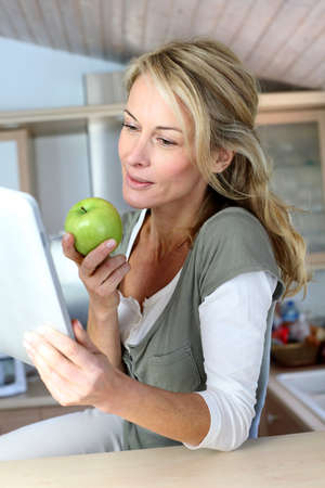 woman apple: Cheerful adult woman websurfing with tablet and eating apple
