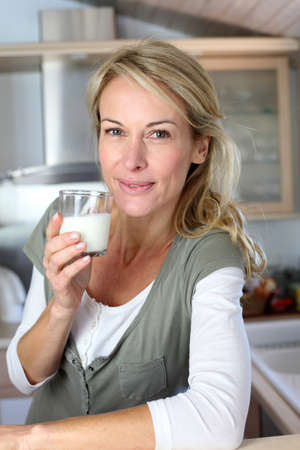 40 years old: Portrait of blond woman drinking milk in home kitchen
