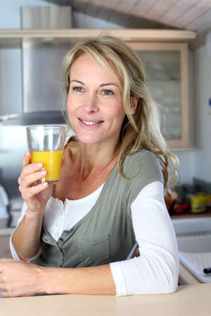 mid morning: Portrait of blond woman in kitchen drinking orange juice