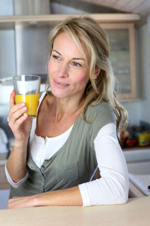 Portrait of blond woman in kitchen drinking orange juice photo