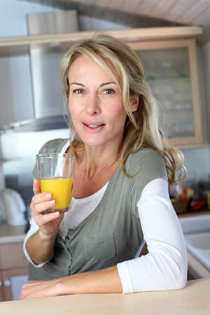 mid morning: Portrait of blond woman in kitchen drinking orange juice