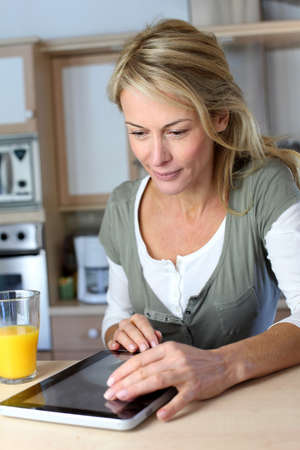 Middle-aged woman using tablet in kitchen  photo