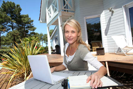 woman 40 years: Teleworker in front of latptop computer at home Stock Photo