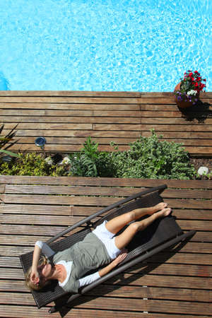 pool deck: Woman relaxing in deck chair by swimming pool