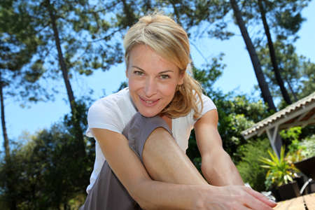 Middle-aged woman doing fitness exercises outside photo