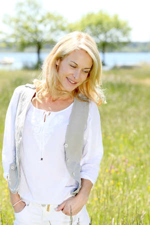 beautiful woman standing in country field in summer time photo