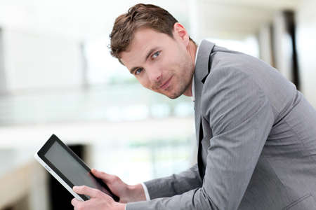Portrait of businessman using electronic tablet in hall photo