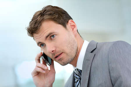 gray suit: Businessman having a phonecall in building hallway