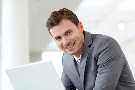 Businessman using laptop computer in entrance hall Stock Photo - 13904935