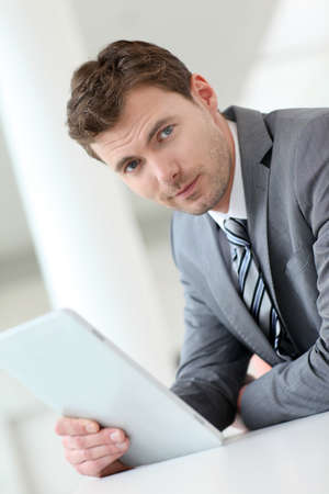 Businessman waiting in hallway with electronic tablet photo