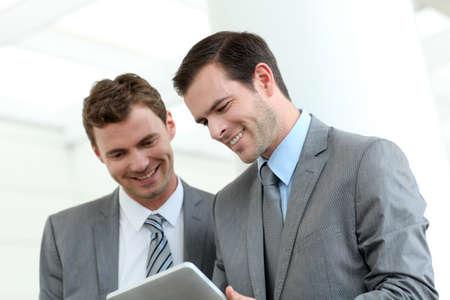 n�gocier: Les partenaires commerciaux qui travaillent dans le couloir avec tablette �lectronique Banque d'images