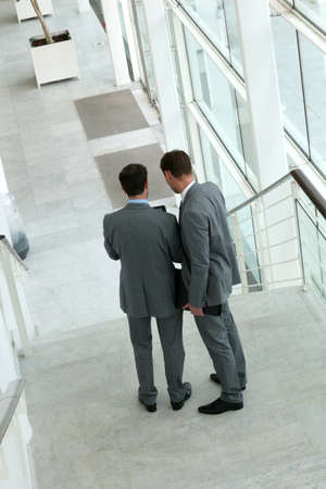 Back and upper view of business people standing in stairs photo