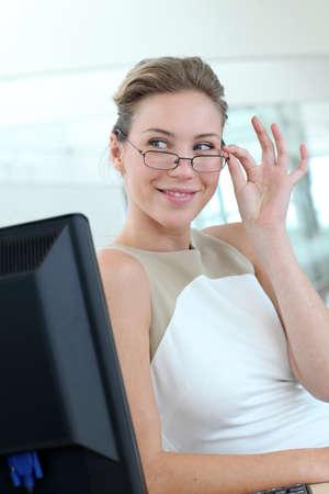 rubia ojos azules: Hermosa mujer de negocios con gafas sentado en la oficina Foto de archivo