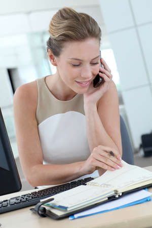 Businesswoman at her desk booking meeting hours on agenda photo
