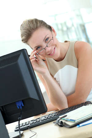 Beautiful businesswoman with eyeglasses sitting in office photo