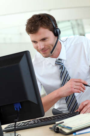 customer service representative: Customer service representative sitting in front of desktop
