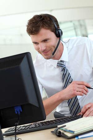 telephone salesman: Customer service representative sitting in front of desktop