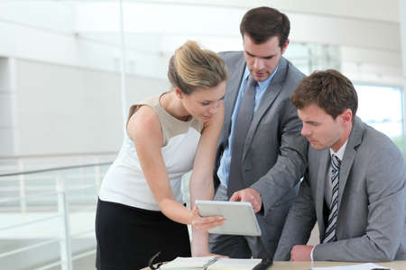 electronic tablet: Group of business people meeting around table